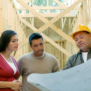 A couple talks to a contractor about plans for their new house.